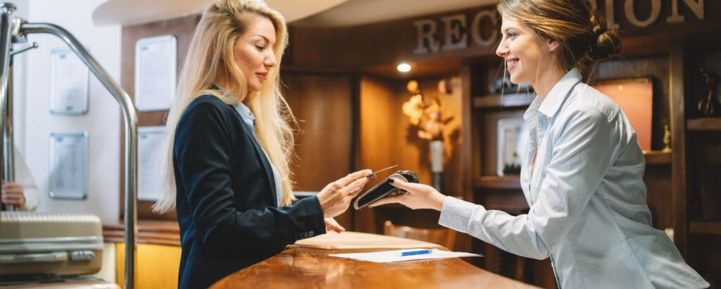 Female using credit card at hotel reception