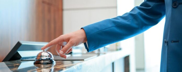 Person ringing bell at hotel desk
