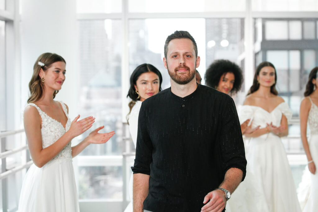 Justin Warshaw of Justin Alexander Design walking among brides in dresses for one of the Marriott Bonvoy Moments